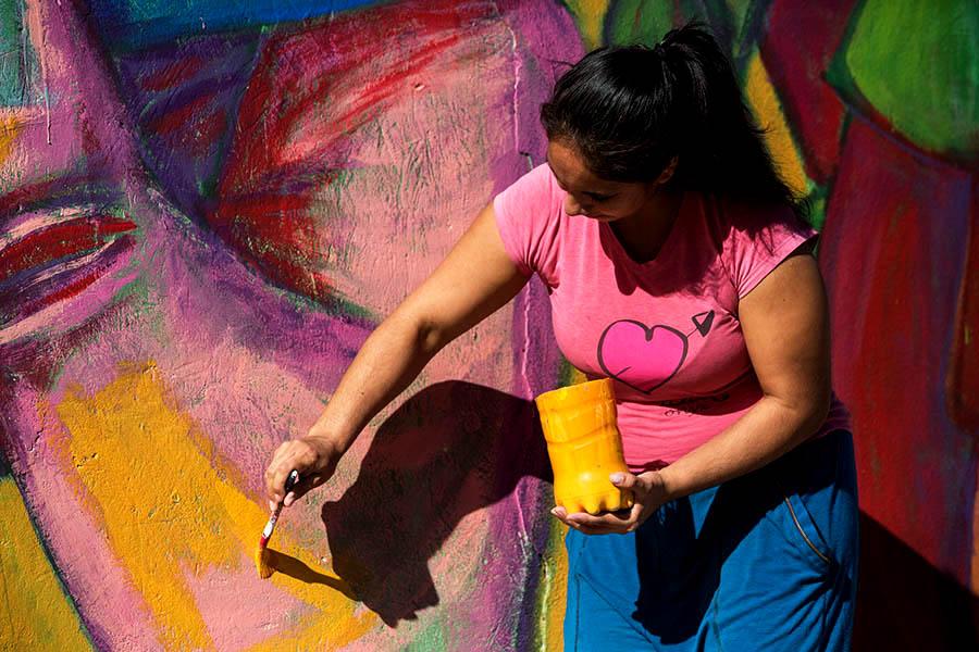 Mujer pintando un mural.