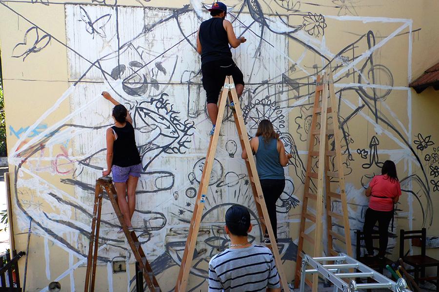 Jovenes pintando un mural.