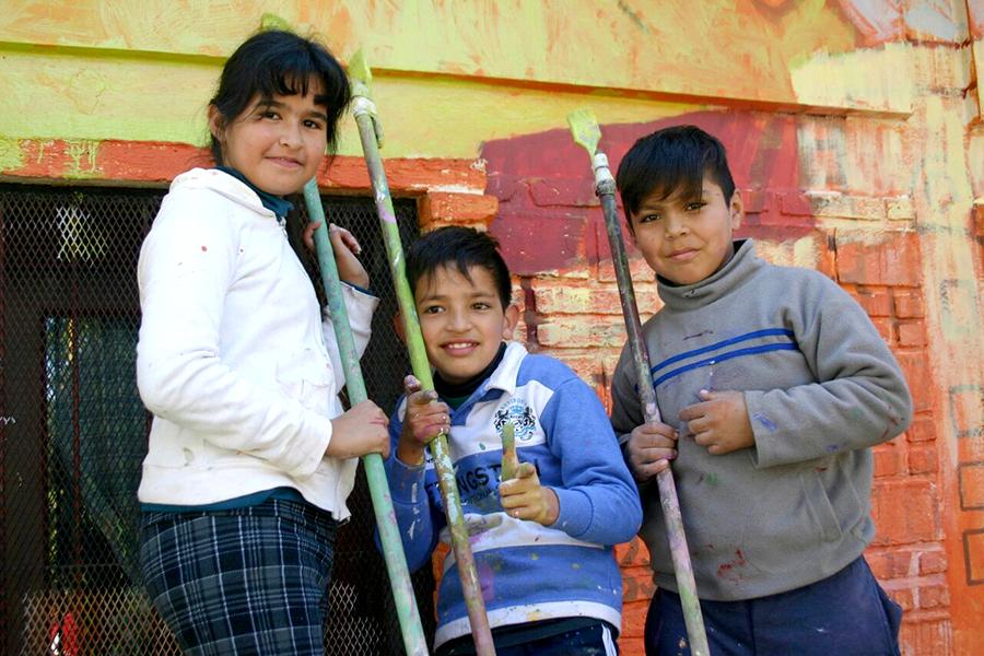 Tres chicos con pinceles grandes.
