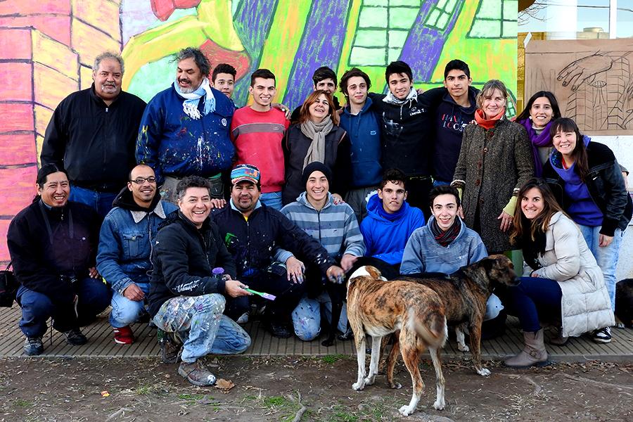Foto de jóvenes frente a un mural.
