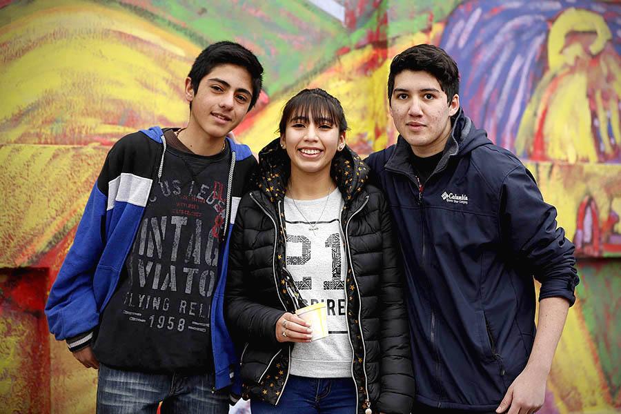 Tres jóvenes frente a un mural.