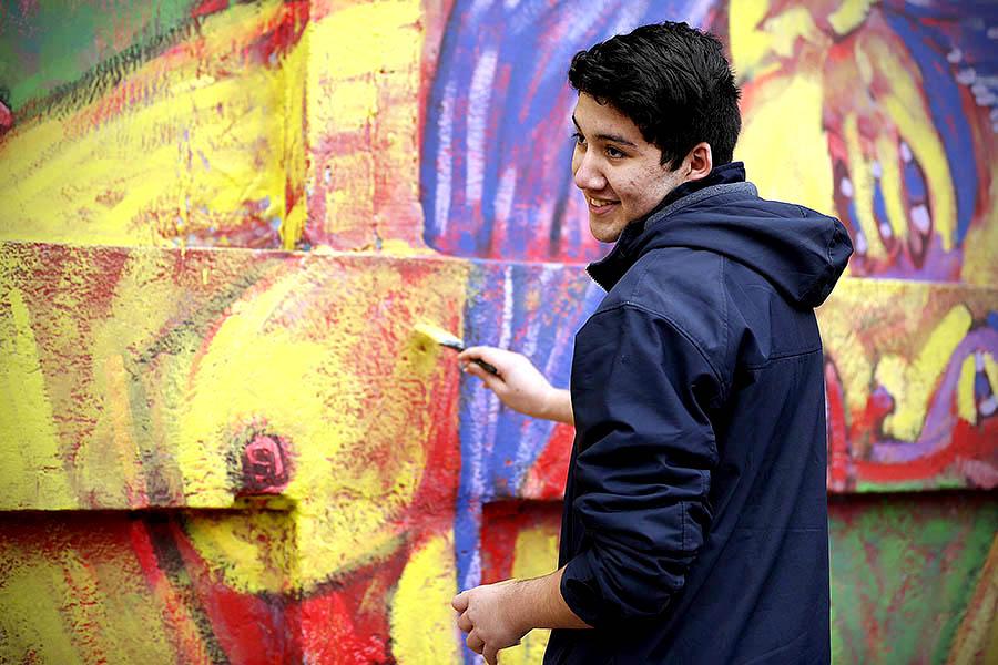Foto de un joven pintando un mural.