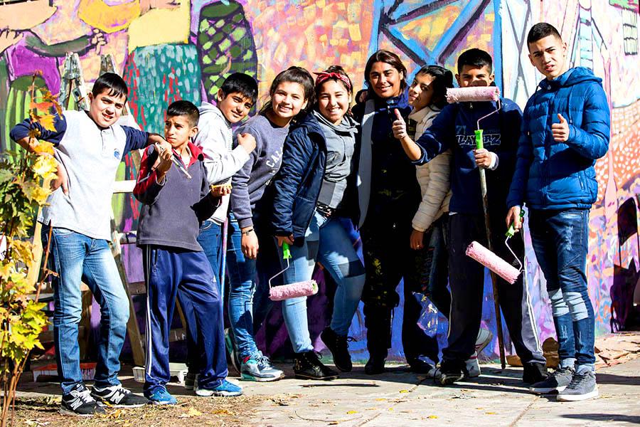 Foto grupal de jovenes frente a un mural.