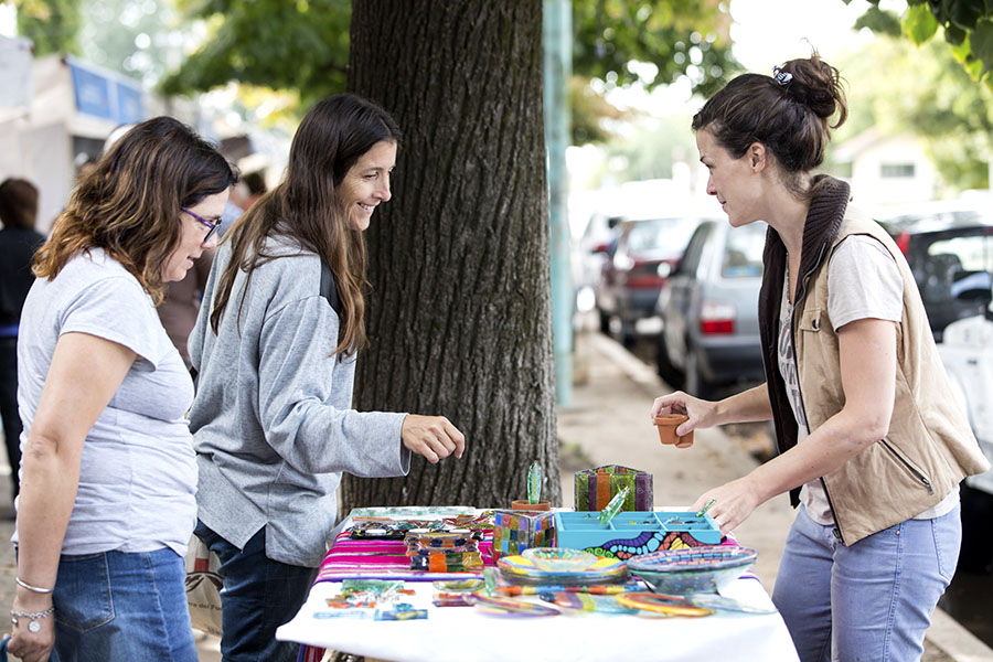 Imagen ilustrativa de artesana de productos de vidrio con dos jóvenes