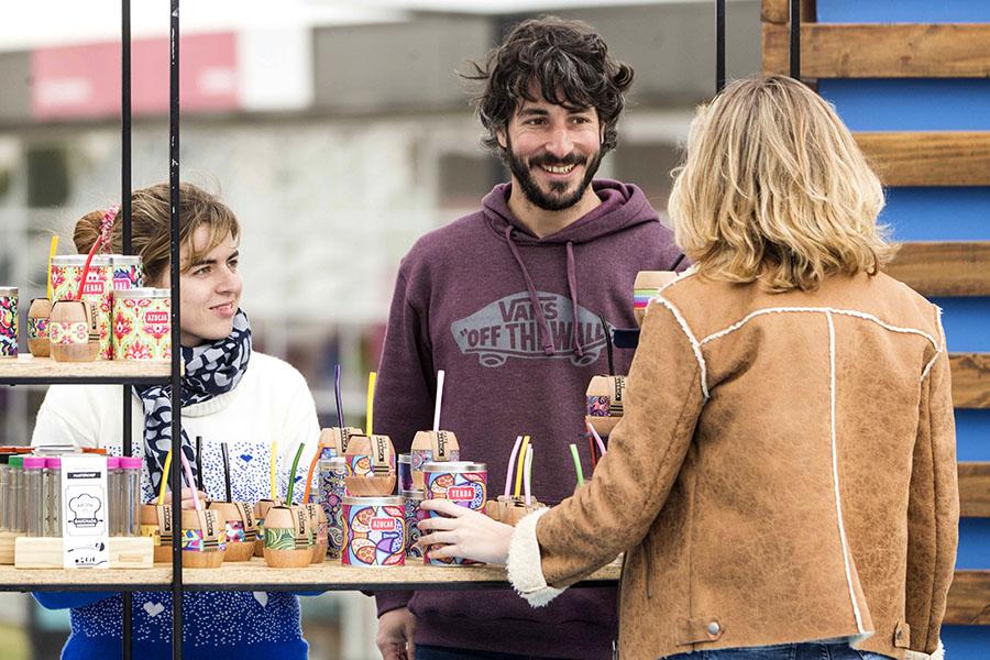Imagen ilustrativa de pareja joven en su puesto de venta de mates artesanales