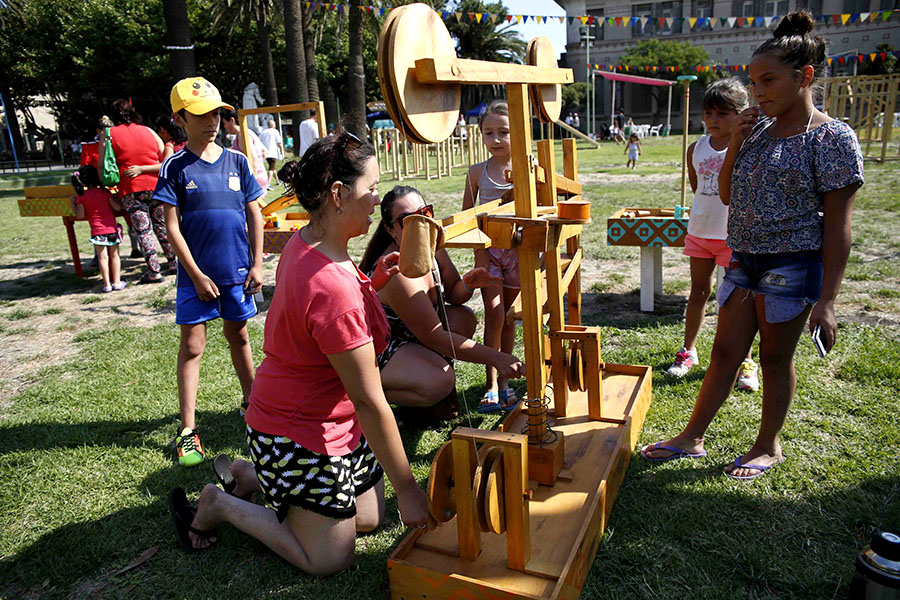 Niña jugando junto a su madre con estructura de madera