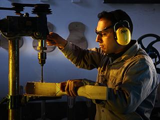 Operario trabajando con una máquina en una fábrica de instrumentos de música