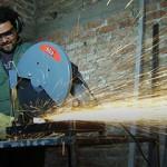 Trabajador cortando un hierro con una amoladora fija.