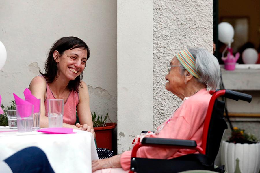 Imagen ilustrativa de joven con abuela en silla de ruedas