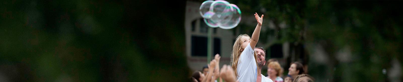 Imagen de una niña con un adulto jugando con una burbuja gigante
