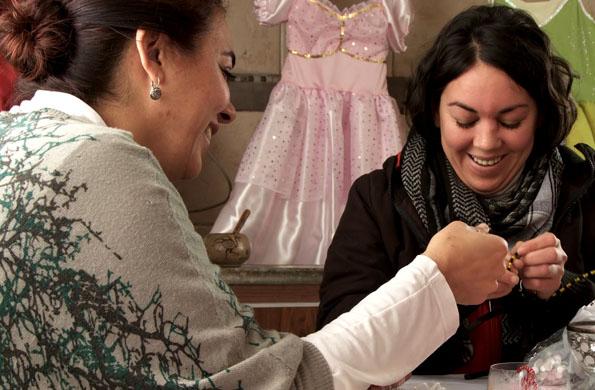 Dos de las trabajadoras de Ilusionarte, confeccionando un disfraz.