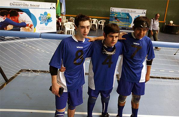 Facundo junto a dos compañeros de equipo en la cancha de golbol.