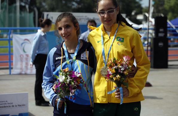Milagros junto a una competidora en la pista de atletismo del CeNARD.