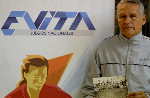 Julio Ayala junto a una foto del equipo que integró en los Juegos Evita de 1955.