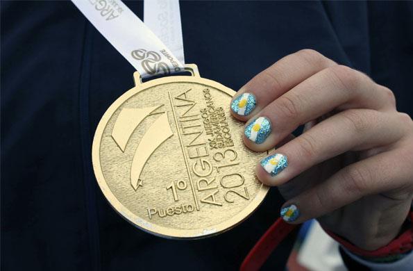 Josefina Simes muestra orgullosa su medalla dorada por su desempeño en salto en alto.