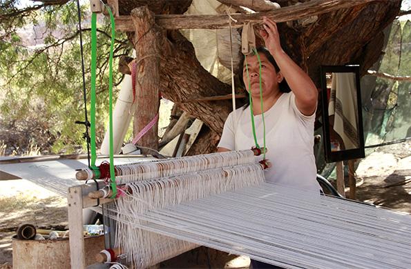 Una de las artesanas elaborando el típico poncho salteño para comercializar luego en la feria.
