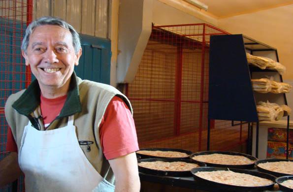 Jorge junto a su producción de pizzas, a punto de hornear.