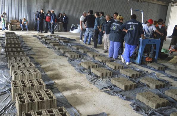 Trabajadores de Benavidez producen bloques de hormigón para construír un ingreso de lanchas.