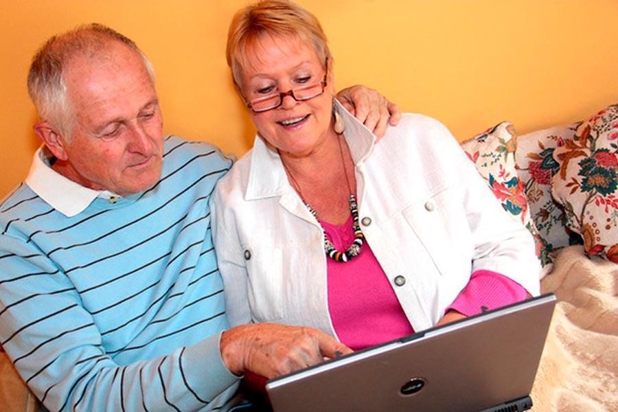 imagen de una mujer junto a su bebe frente a una computadora portátil