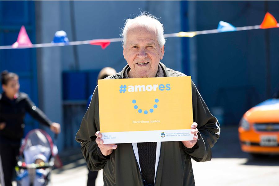 Adulto mayor sosteniendo el cartel de la Campaña #Amores