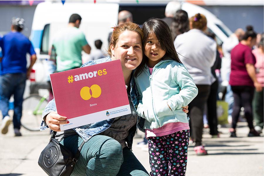 Mujer y niña sosteniendo el cartel de la Campaña #Amores