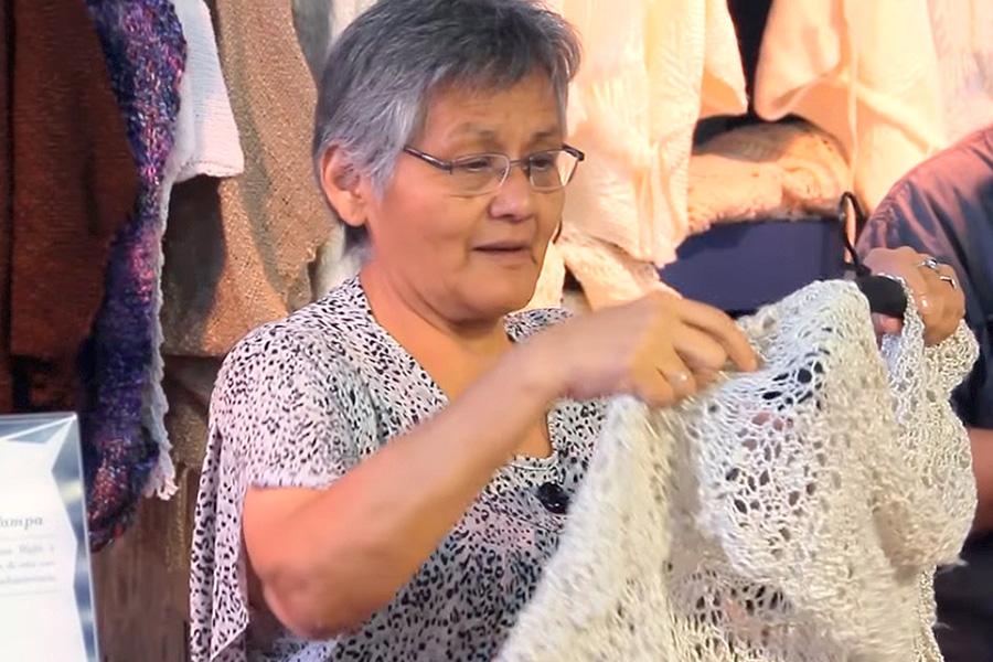 Susana toma en sus manos uno de los tejidos.