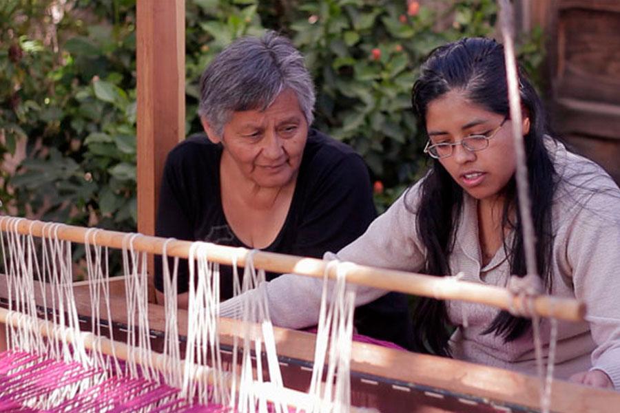Susana Prado mientras le enseña la técnica del telar a una de las jóvenes integrantes de Muspay.