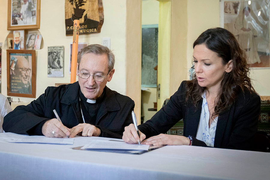 Carolina Stanley firmando el acuerdo con Monseñor Joaquín Sucunza.