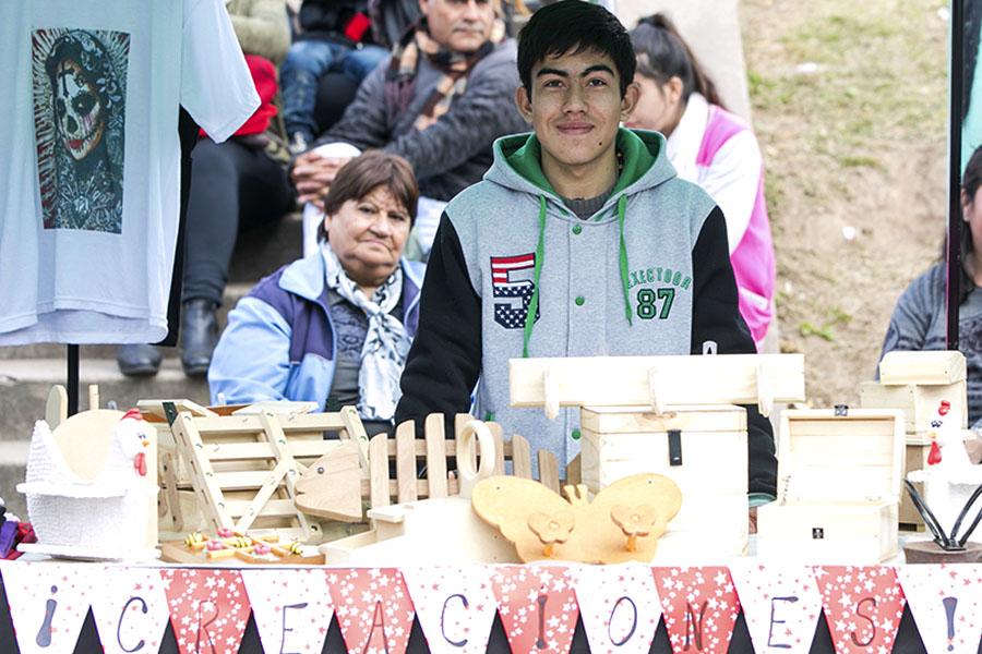 Joven en su stand de artesanías de madera