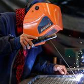 Hombre soldando rejilla de metal