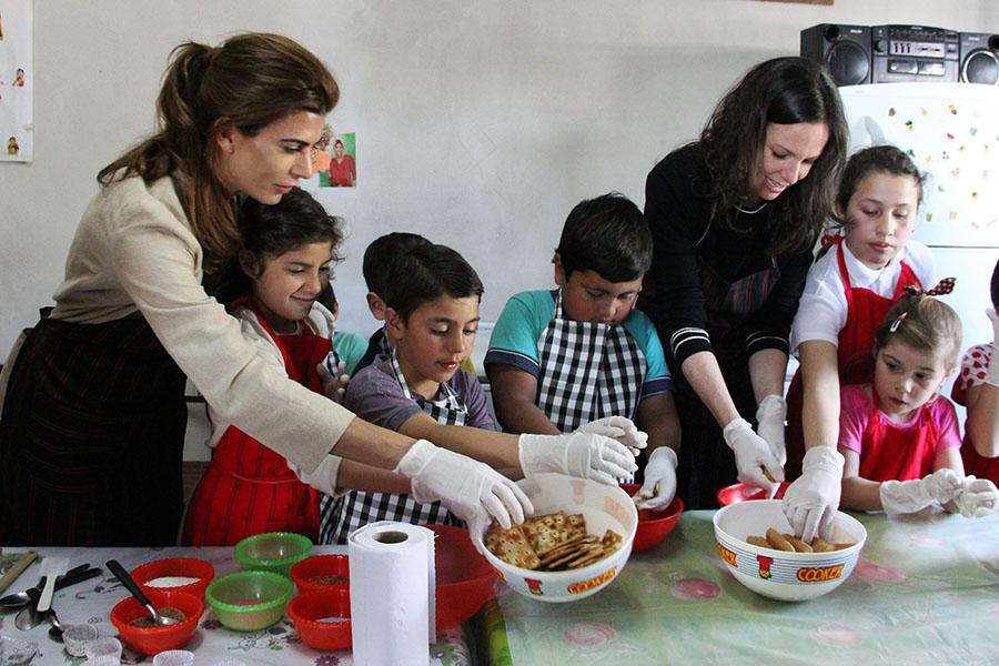 La ministra y la primera dama cocinan junto a los chicos que participan de los talleres del centro.