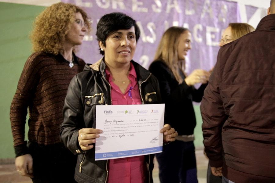 Alejandra muestra orgullosa su diploma de finalización de estudios..