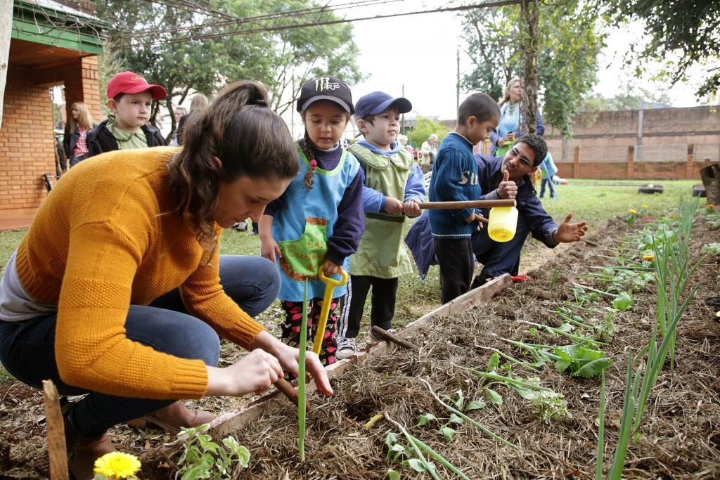 Fotografía ilustrativa de niños cultivando en la huerta.