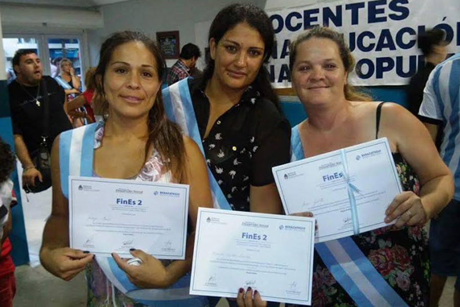 Fotografía ilustrativa de Cintia y dos compañeras sosteniendo el título de FinEs.