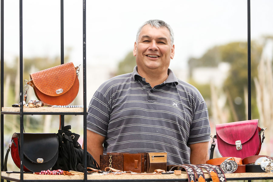 Fotografía ilustrativa de un señor vendiendo carteras y cinturones.