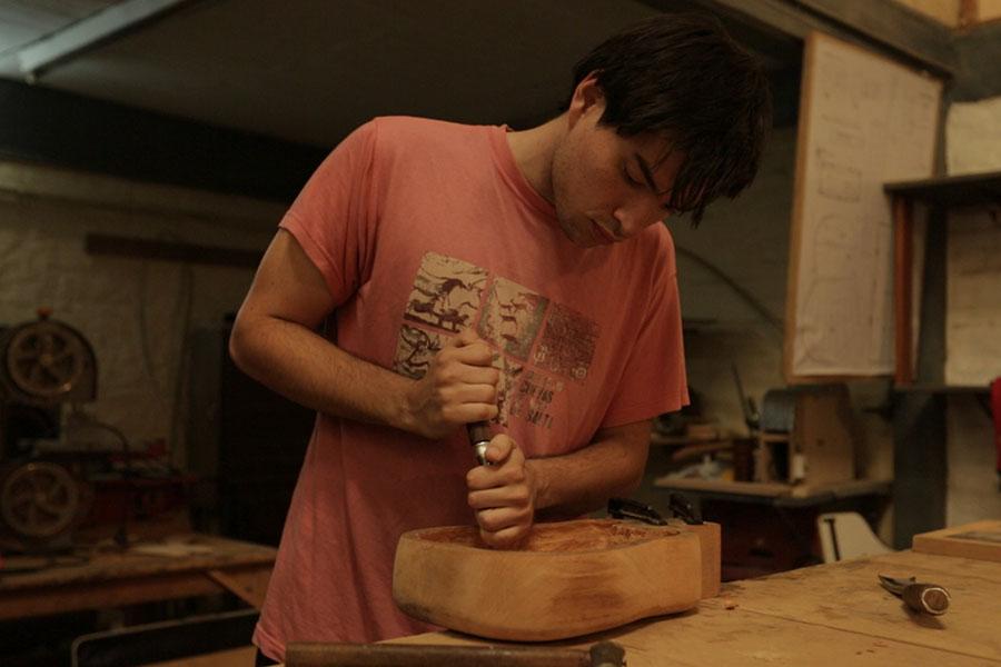Imagen ilustrativa de un artesano elaborando un violín.