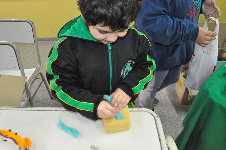Imagen ilustrativa de un niño fabricando un muñeco de vellón de lana.