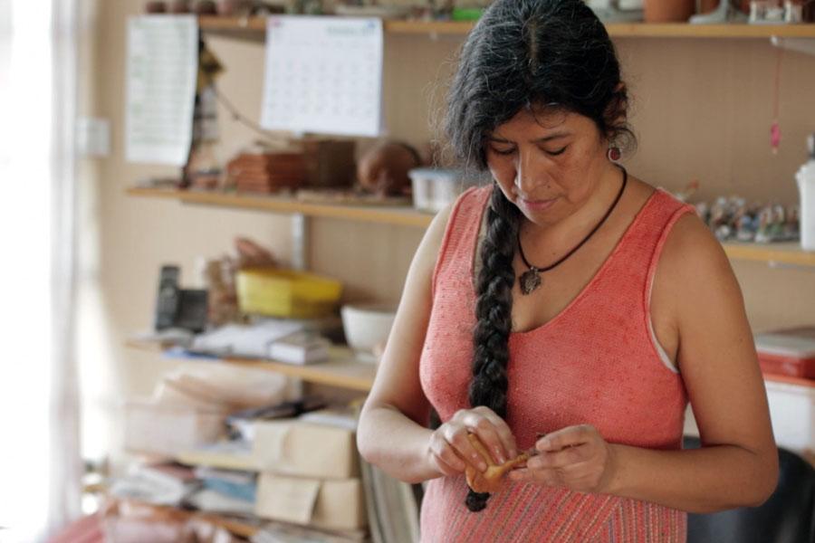 Fotografía ilustrativa de una señora haciendo artesanías.