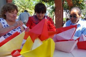 Imagen ilustrativa de adultos mayores haciendo barcos de papel