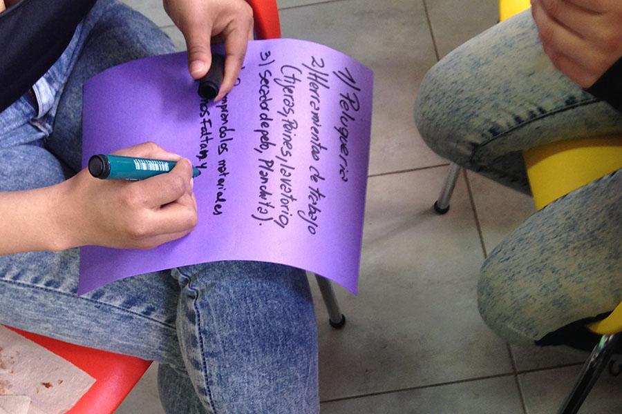 Imagen ilustrativa de una chica escribiendo en una cartulina.