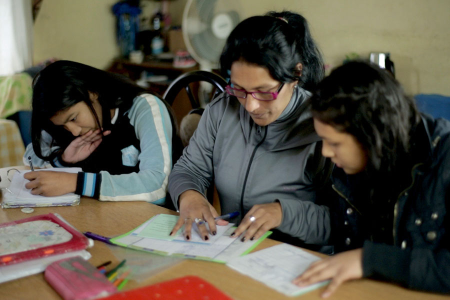 Fotografía ilustrativa de una mujer estudiando con sus hijos.