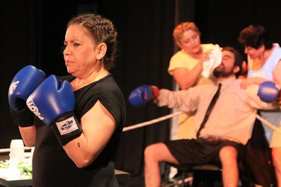 Fotografía ilustrativa de una mujer con guantes de boxeo y un hombre golpeado atrás.
