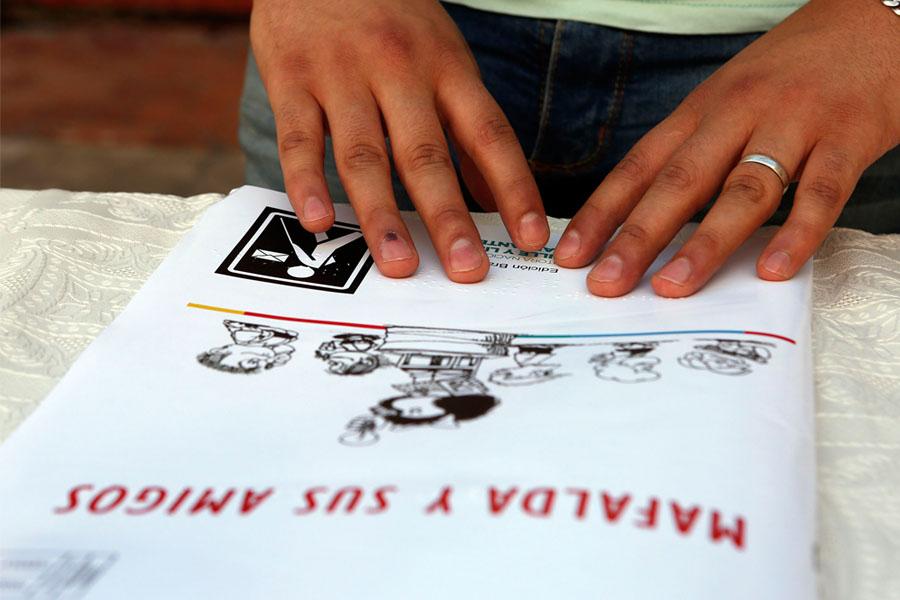 Fotografía ilustrativa de una persona leyendo en braille las historias de Mafalda.