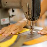 Imagen ilustrativa de manos y una máquina de coser