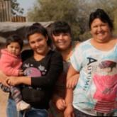 Imagen ilustrativa de tres mujeres sonriendo y una niña en brazos