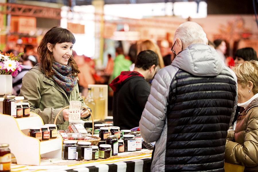 Imagen ilustrativa de joven vendiendo en su puesto de mermeladas