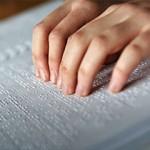 Joven leyendo en codigo Braille