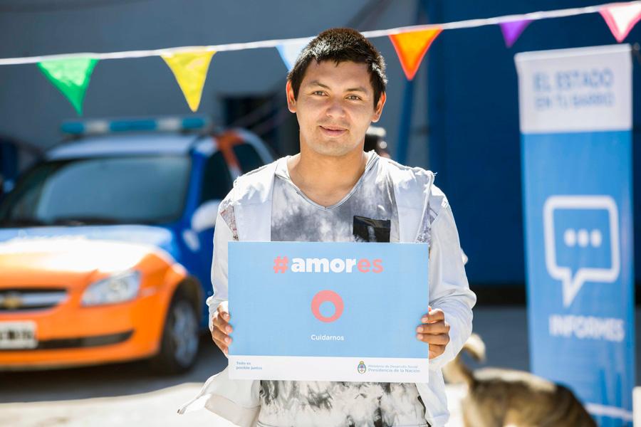 Joven sosteniendo el cartel de la Campaña #Amores