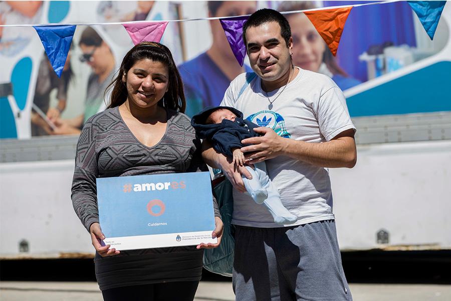 Familia sosteniendo el cartel de la Campaña #Amores