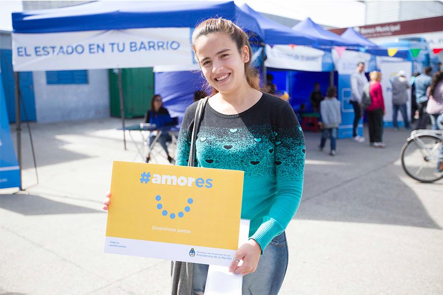 Mujer adolescente sosteniendo el cartel de la Campaña #Amores